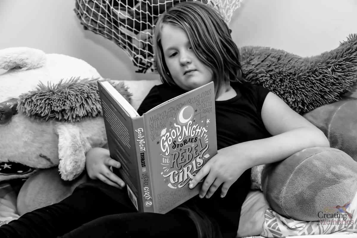black and white photo of girl reading good night stories for rebel girls