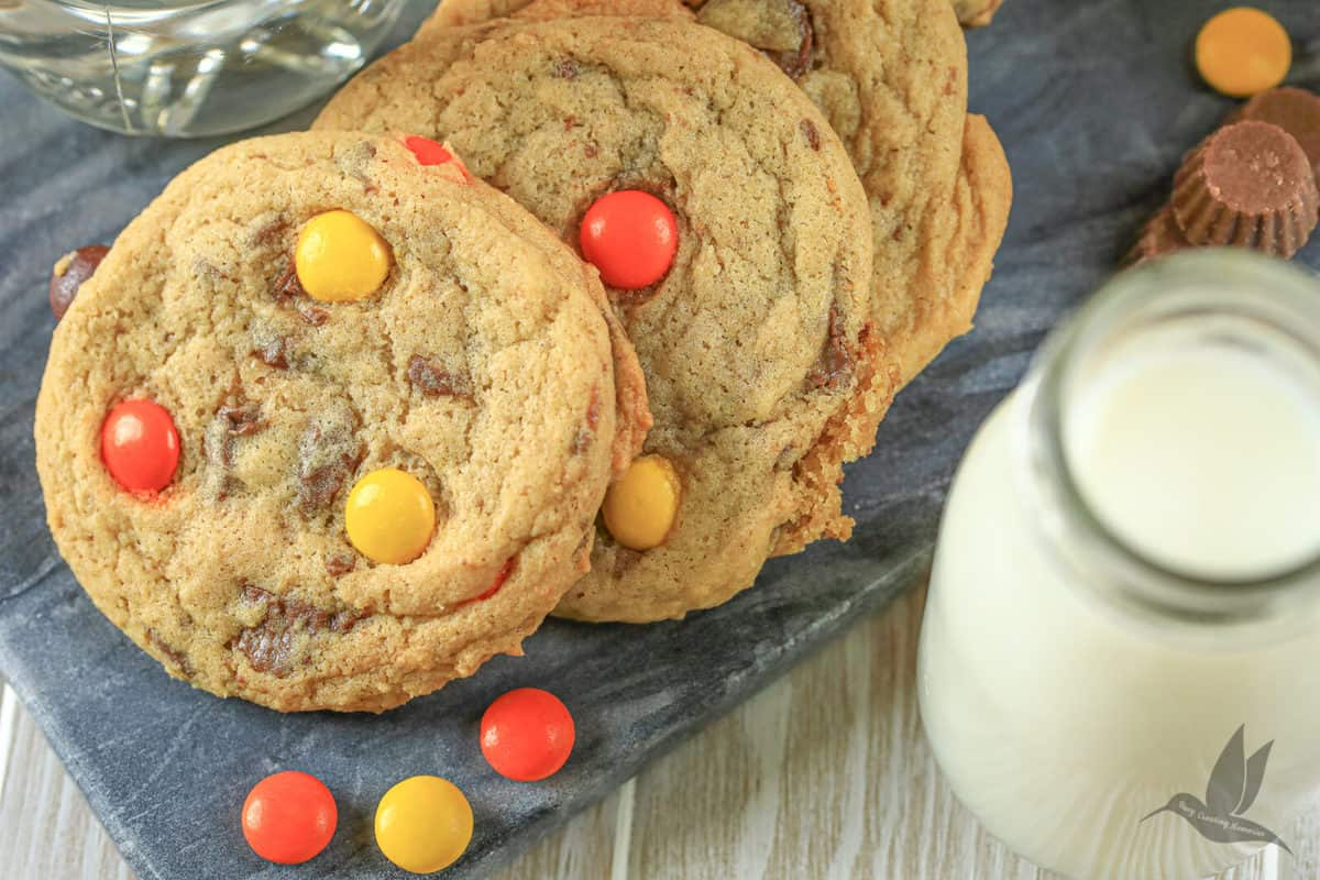 Chocolate chip cookie up cloase with Reese's Pieces candies and a glass of milk