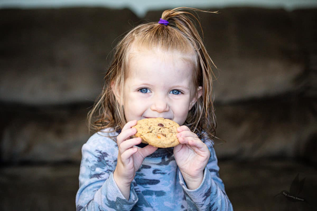 Little girl holding a cookie and smiling