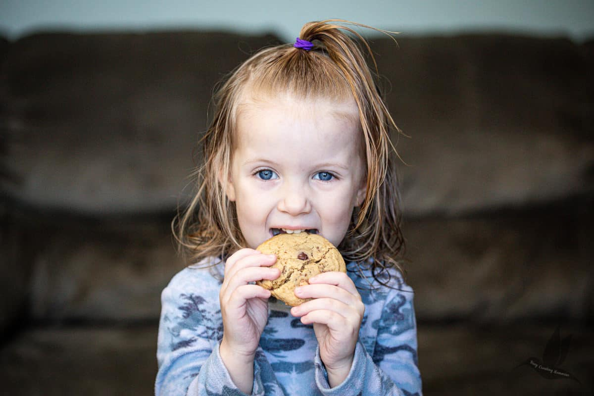 young girl biting into a chewy chocolate chip cookie