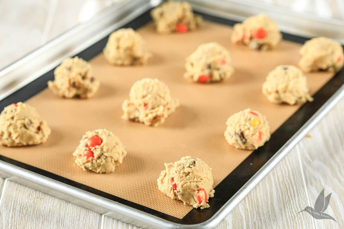 chocolate chip cookie dough in balls on baking sheet