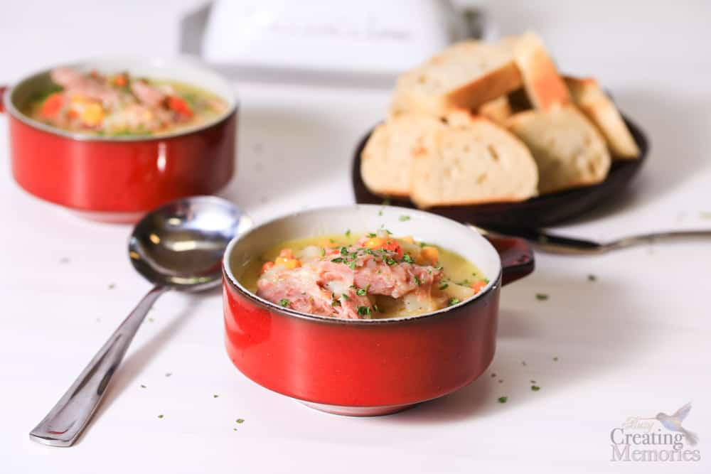 two bowls of ham bone soup with a slice of bread and a soup spoon near by