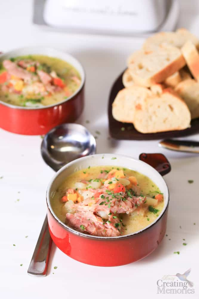 two bowls of creamy ham bone soup with sliced bread