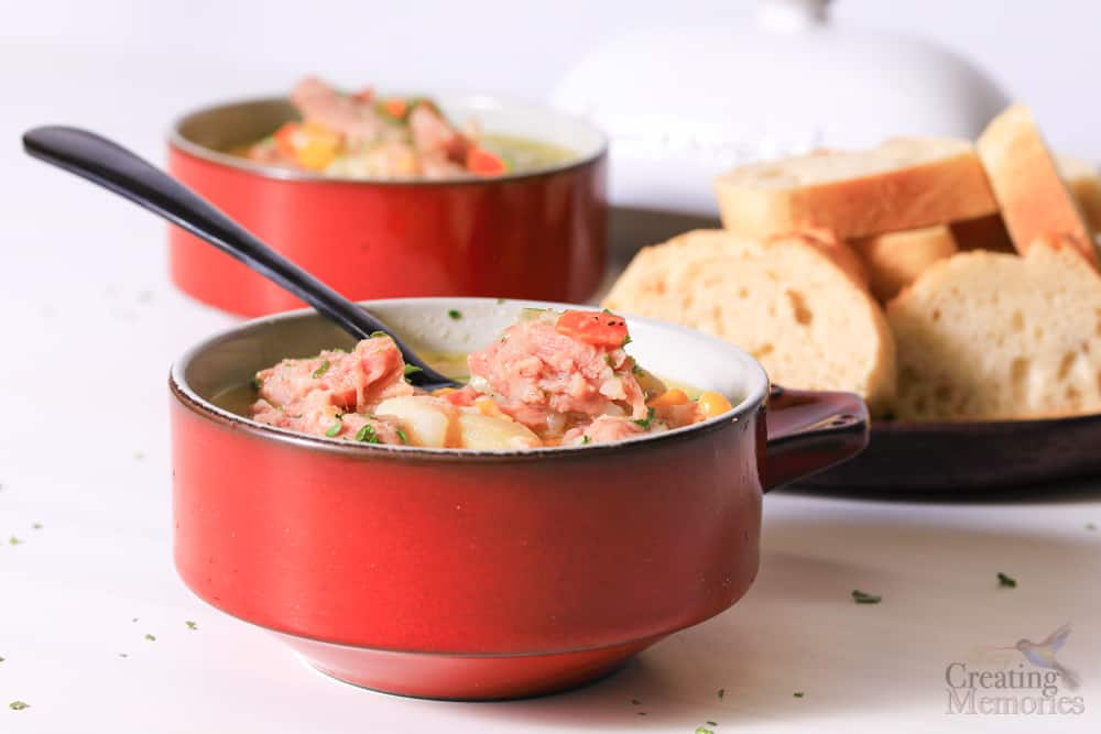 Side angle of a red bowl filled with ham and potato soup