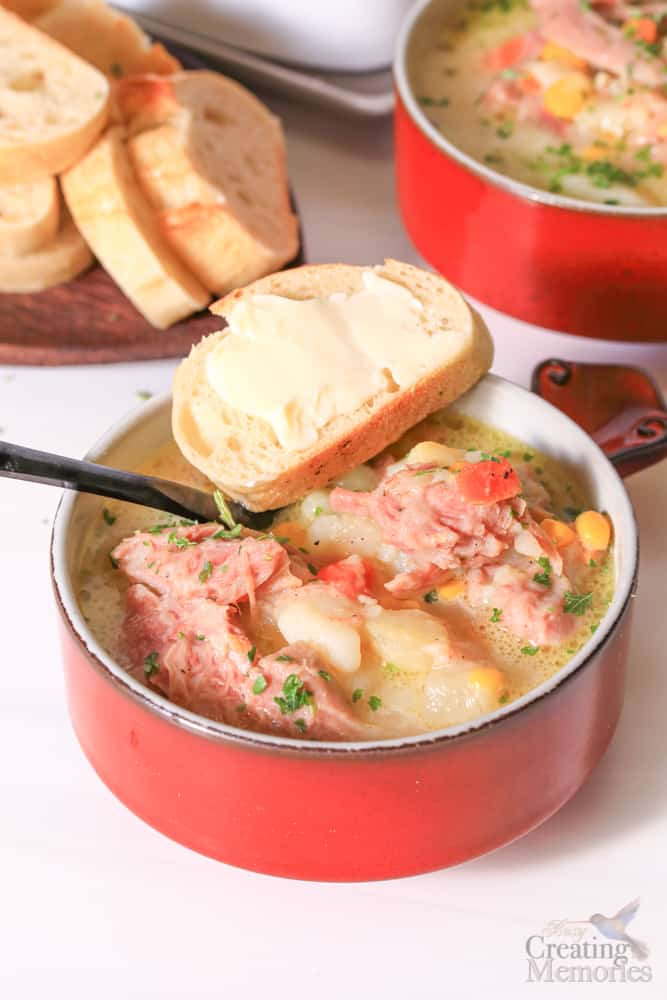 close up photo of ham and potato soup in a red bowl with a slice of buttered bread