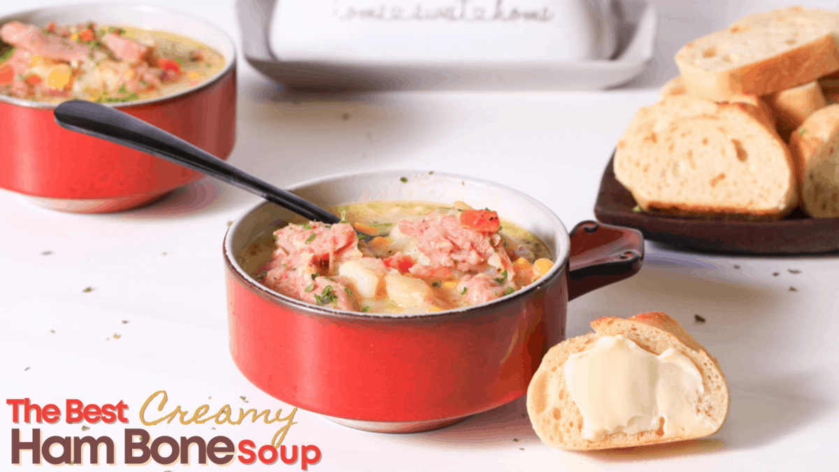 Fresh Bowl of creamy ham bone soup in a red bowl with a slice of buttered bread